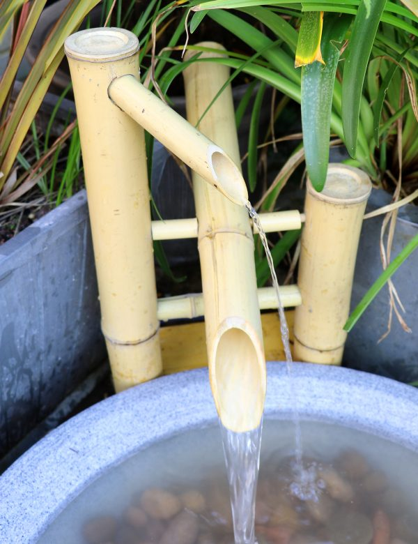 bamboo water spout flowing into round pond